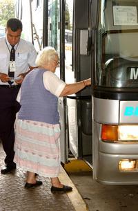 Senhora idosa sobe em ônibus