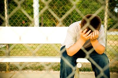 Inclusive - bullying - imagem de um menino sentado tapando o rosto com as mãos.