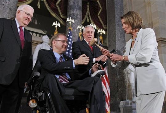 A Presidente do Congresso, Nancy Pelosi, passa para o congressista Jim Langevin, o bastâo e o assento da Presidência da Casa pela primeira vez a uma pessoa com deficiência