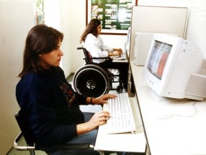Duas mulheres sentadas ao computador, trabalhando, uma delas, em segundo plano, sentada em cadeira de rodas.