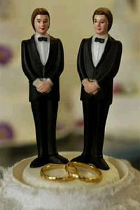 Casamento gay, dois bonecos masculinos e duas alianças sobre um bolo de casamento