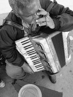 Artista de rua cego, tocando acordeon