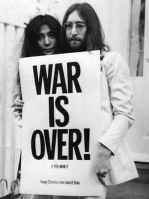 """John Lennon e Yoko Ono carregando o cartaz """"War is over if you want it"""" que espalharam em todo o mundo"""