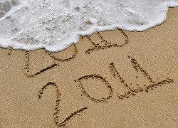 Uma onda do mar apaga da areia a data de 2010 e preserva a de 2011
