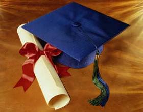 Chapeu de formatura azul e diploma enrolado atado por fita vermelha
