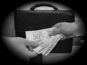 Foto em preto e branco - Uma mao passa notas de 50 reais enquanto outra recebe sobre o fundo de uma maleta preta