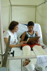 Menino com duas pernas engessadas lê livro ao lado de professora