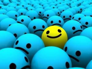 Uma bolinha amarela sorridente no meio de várias bolinhas azuis tristes