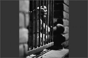 Foto em preto e branco mostra mão segurando grade.