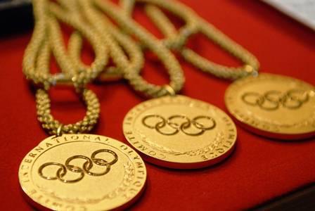 Três medalhas olímpicas de ouro sobre fundo vermelho