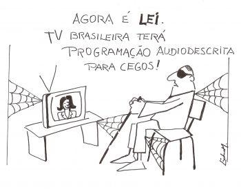"""""""Agora é Lei. TV brasileira terá programação audiodescrita para cegos!"""" Na charge um homem cego, óculos escuros e bengala nas mãos, está sentado em uma cadeira em frente à TV ligada. Há várias teias de aranha no recinto, sendo uma entre a parede à esquerda e a TV, uma entre o rack da TV e a bengala do cego, outra entre a perna do cego e a cadeira e a última, entre suas costas e a parede à direita."""