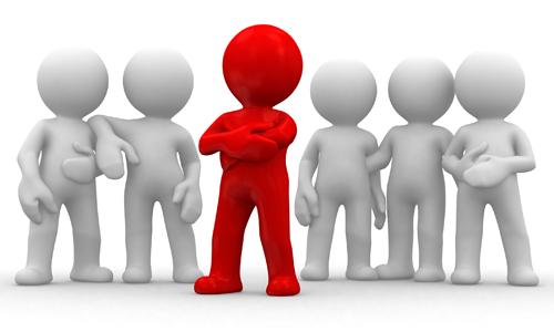 Inclusive - Discriminação - Preconceito - Um boneco em vermelho aparece diante de dois grupos de bonecos grandes.