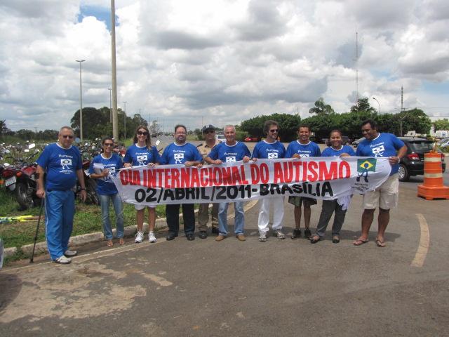 Ativistas de camiseta azul carregam faixa onde se le Dia Internacional do Autismo - 2 de abril de 2011 - Brasilia