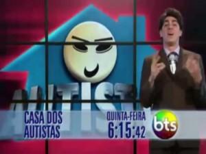 """O """"comediante"""" Marcelo Adnet em frente ao logo do programa Casa dos Autistas, uma casa azul com uma cara sorridente amarela"""