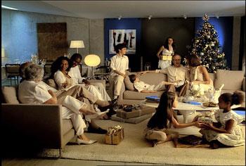 Em uma sala, com arvore de natal ao fundo, varias pessoas vestindo branco sentadas num sofa, meninas brincando sentadas no chao.