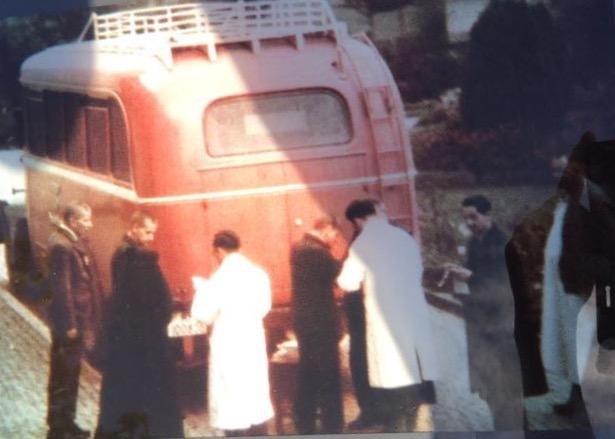 foto colorida, onubus de costas, 2 pessoas com jaleco branco e 3 pessoas de roupa preta.