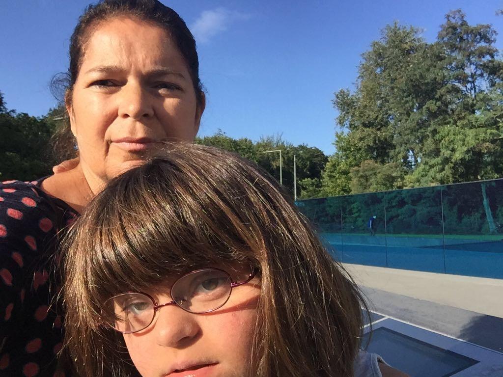 Patricia Almeida e a filha Amanda com o videro azul do memorial ao fiundo.