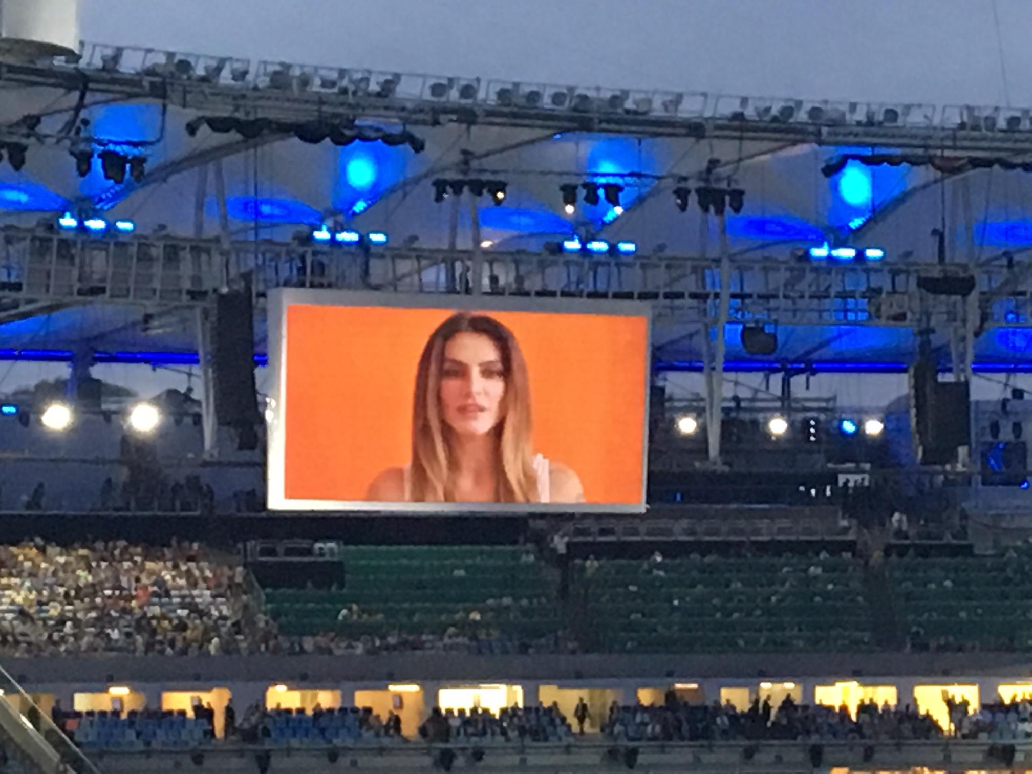 no estadio, telao mostra fundo laranja e o rosto da atriz cleo pires em primeiro plano.