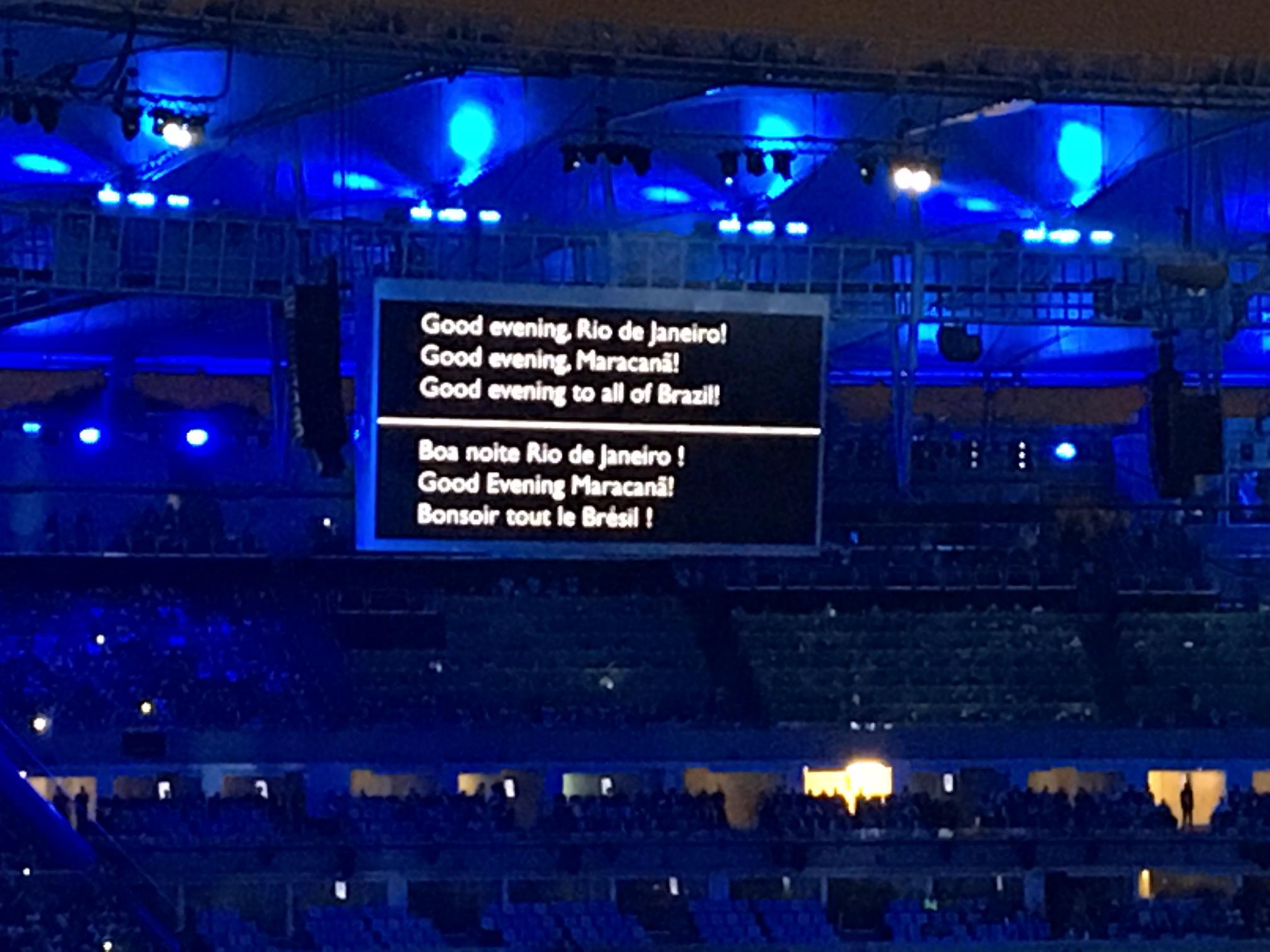 telao no estadio mostra legendas sobre fundo preto, em ingles e portugues - bem-vindo ao Rio de Janeiro.