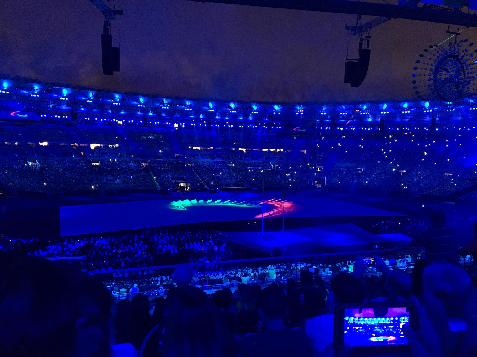 no estadio do maracana escuro, o simbolo dos jogos paralimpicos acesos nas cores verde, azul e vermelho.