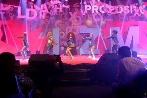 em palco com luz rosada e palavras escritas no fundo, a cantora carol conka e bailarinos.