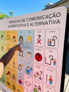 dedo de criança aponta para figura na prancha de comunicação.