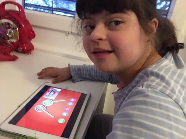 menina sentada em frente a tablet com o vídeo canta e lê, olha e sorri para a câmera.