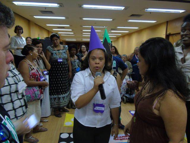 jovem participante da mostra fala ao microfone em sala, em meio a outros participantes. ela tem chapeu em cone roxo.