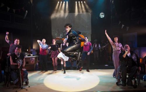 Num palco, guitarrista pula com guitarra na mao, com dois cadeirantes ao lado.