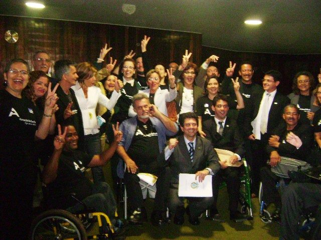 várias pessoas com e sem deficiência, muiats com camiseta acessibilidade já, sorriem e comemoram a aprovação da convenção na câmara.