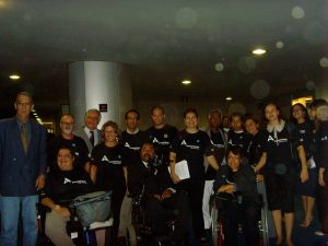 grupo de pessoas com e sem deficiencia com camiseta preta escrito acessibilidade.