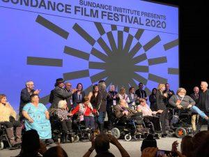 grupo de pessoas, várias em cadeira de rodas, no palco do festival de cinema Sundance 2020.