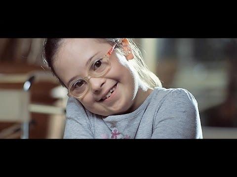 menina com sindrome de down de oculos sorri para a camera.