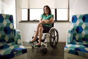 mulher sentada em cadeira de rodas, sorrindo.