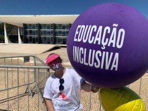 menina segura balao roxo em frente ao supremo escrito educacao inclusiva. ela esta de mascara.