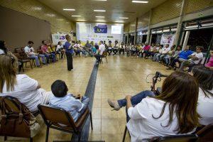ginasio, com pessoas sentadas em cadeiras fazendo uma grande roda. duas pessoas ao centro.