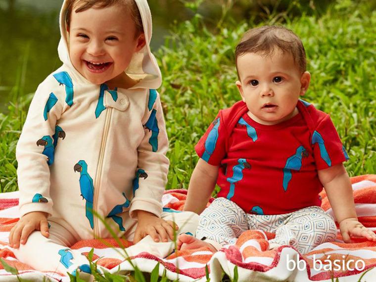 dois bebes sentados em cobertor em cima da grama. um deles tem sindrome de down.