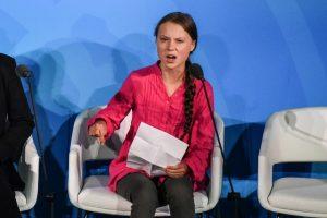 menina sentada em cadeira falando.