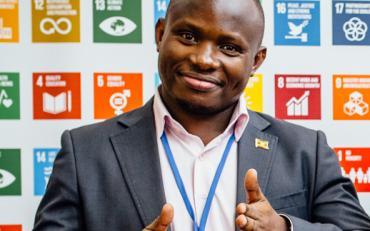 homem sorrindo faz sinal de ok, como dedo pra vima, em frente a um cartaz onde se veem os objetivos sustentaveis da ONU.