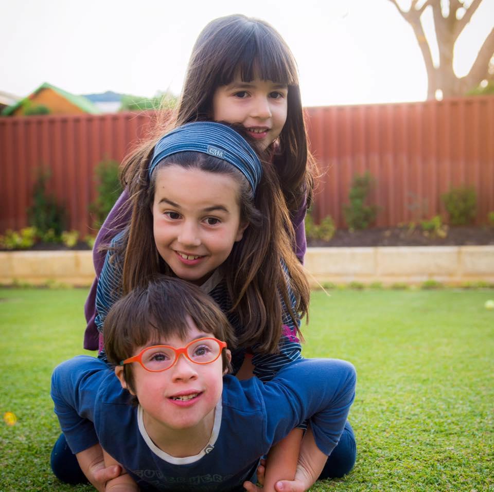tres criancas, uma em cima da outra num gramado. um menino de oculos vermelhos, com sindrome de down por baixo, uma menina por cima e outra menina por cima.