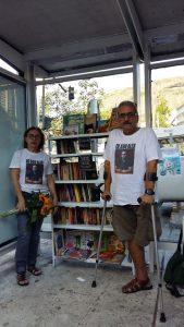 um homem e uma mulher, estante de livros em ponto de onibus.