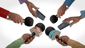 Seis mãos segurando microfones em entrevista coletiva