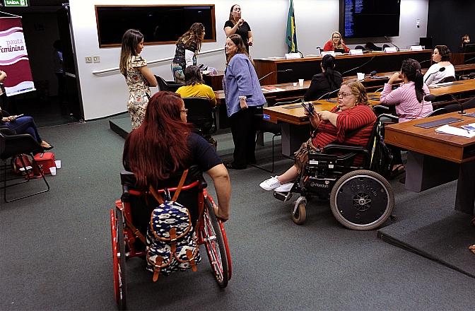 mulheres em cadeiras de rodas na sala da comissao.