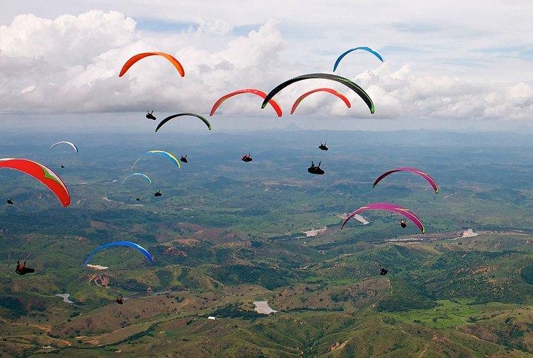 varios paraquedas coloridos voando no ceu e um campo verde abaixo.