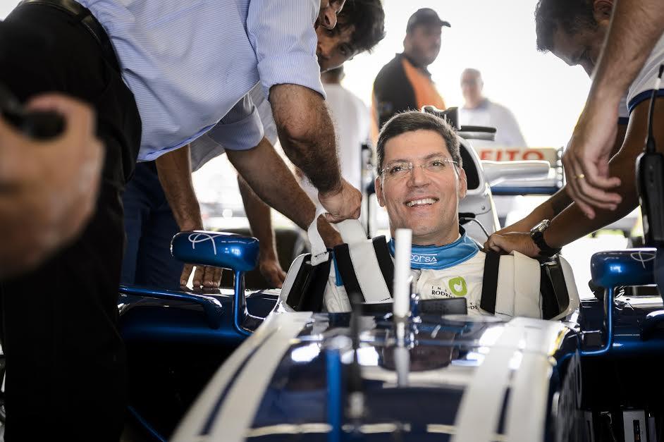 rodrigo mendes sentado em um carro de corrida, sorrindo.
