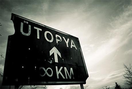 Uma placa de trânsito indica o destino de Utopia, para a frante, a uma distância infinita, representada pelo símbolo matemático do 8 horizontal.