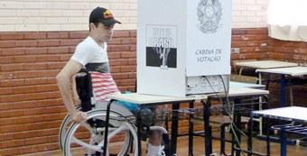 homem em cadeira de rodas atras do protetor da urna.