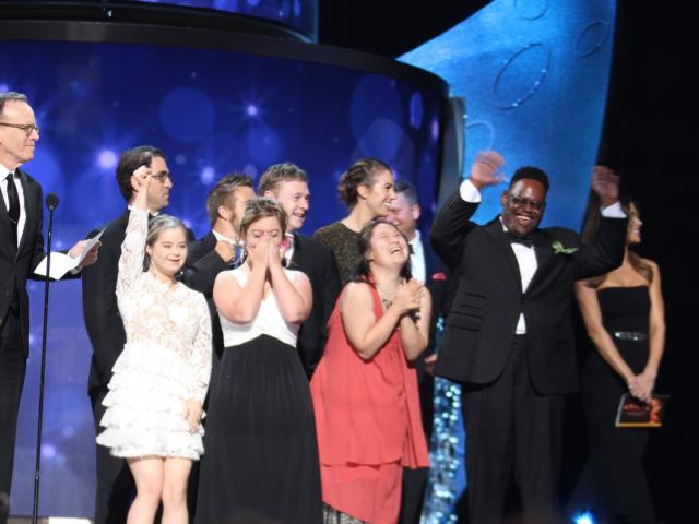 elenco e equipe de born this way no palco celebrando o prêmio Emy.