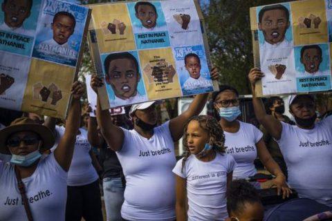 pessoas em manifestação com cartazes com a foto do adolescente morto. alguns usam máscara.